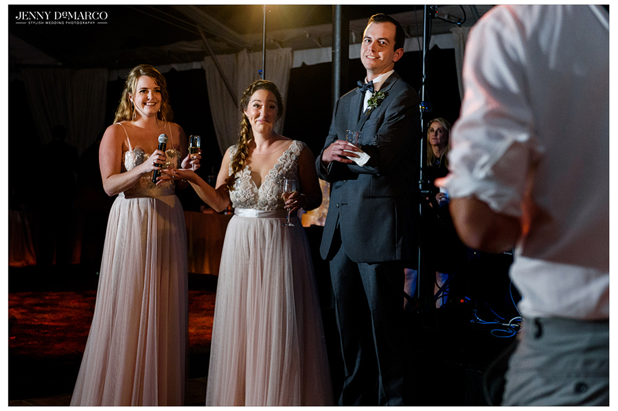 Bridesmaids and groomsmen give toasts as the bride and groom watch during the wedding reception.