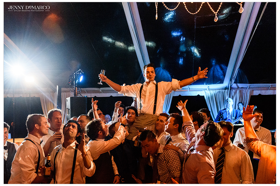 The groom is lifted up on the shoulders of guests at the wedding reception.