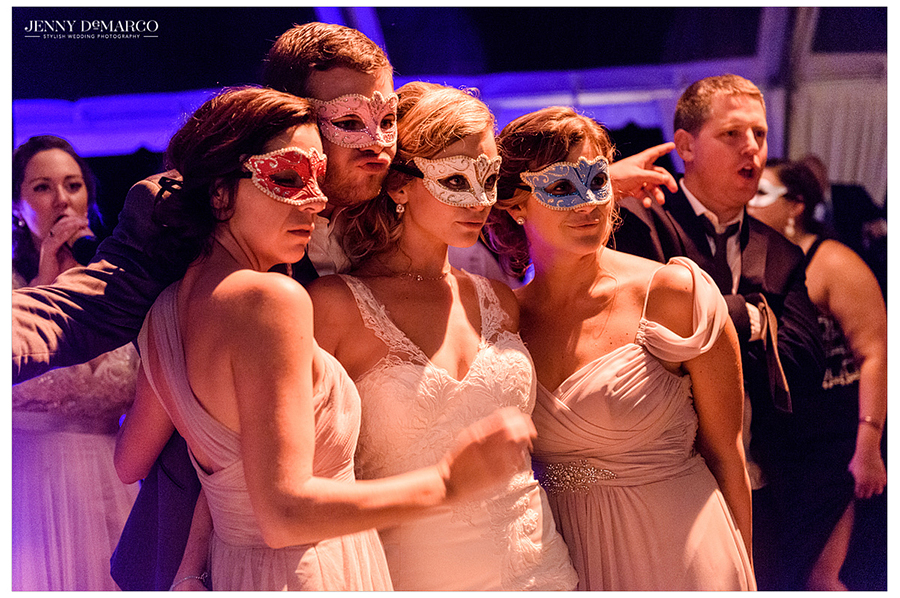 The bride and guests pose together for a photo, wearing colorful masks, during the wedding reception.
