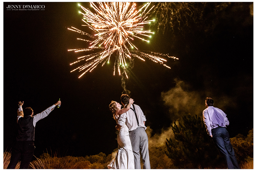 The bride and groom and their guests celebrate outdoors under fireworks at the wedding reception.