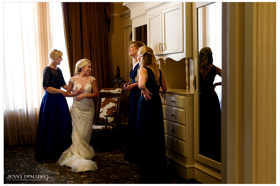 Bridesmaids watch as the bride puts on her wedding dress.