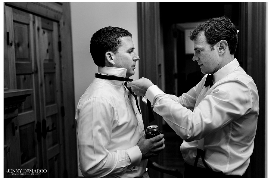 Black and white photo of the groom being assisted with his tie as he prepares for the wedding ceremony.