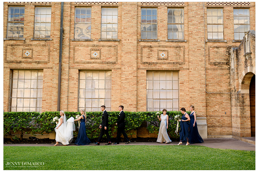 Photo of the bride and members of the wedding party walking outside.