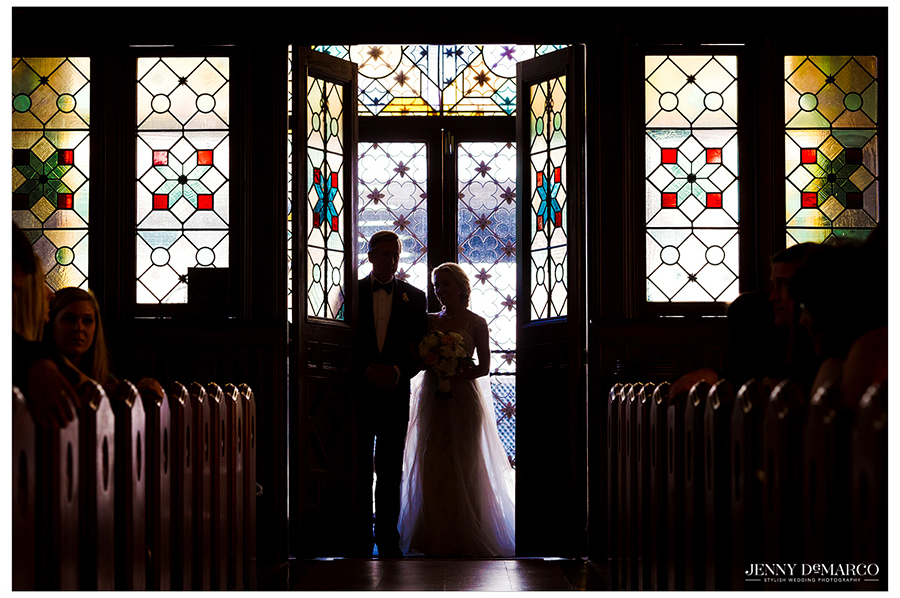 Photo of the bride as she enters Central Christian Church, surrounded by stained-glass windows.