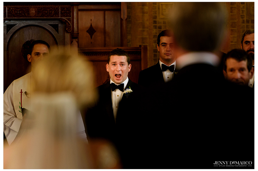 Photo of the groom at the altar as he watches the bride approach.
