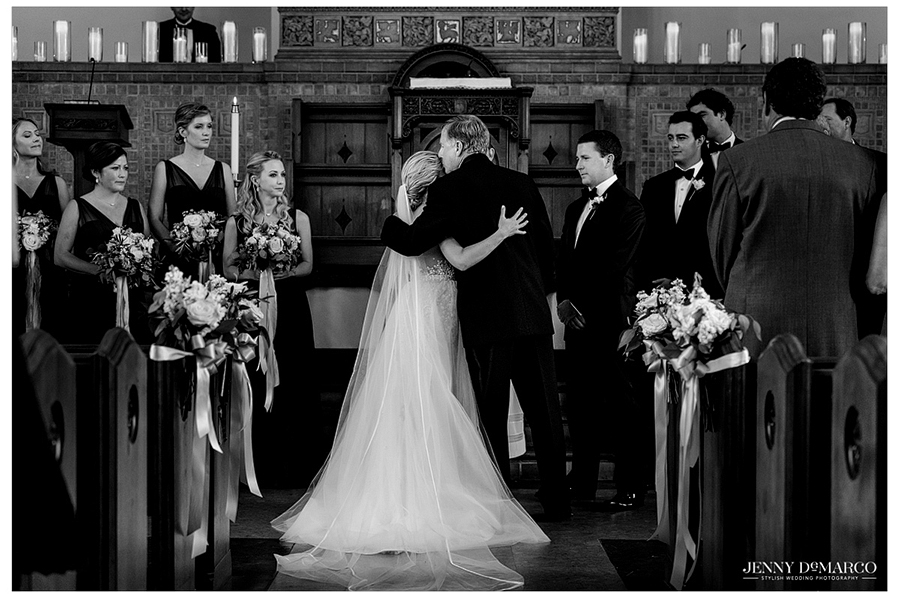 Black and white photo of the bride and groom surrounded by the wedding party at the altar.