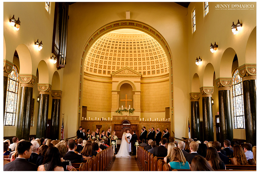 Photo of the bride and groom as they stand at the altar of Central Christian Church, as the wedding guests watch.