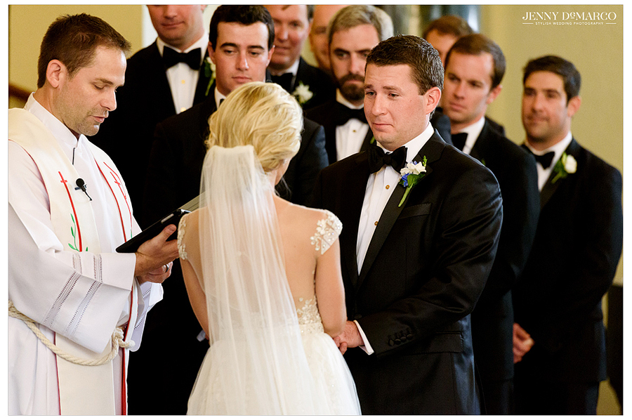 Photo of the bride, groom, and groomsmen at the altar of Central Christian Church during the wedding ceremony.