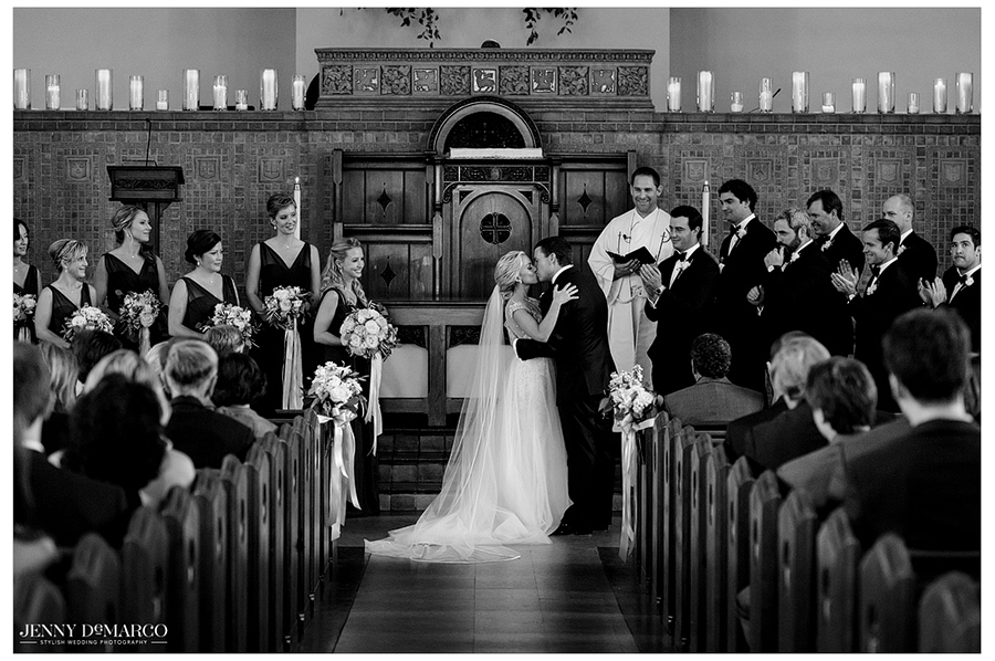 Black and white photo of the bride and groom sharing their first kiss during the wedding ceremony.