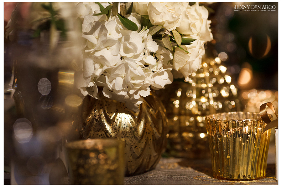 Detail photo of the white flowers and gold table decor at the wedding reception.