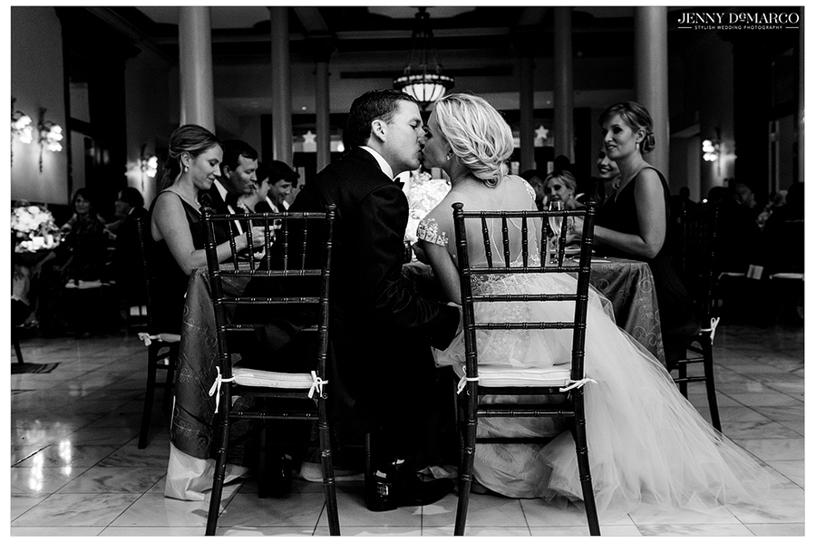 Black and white photo of the bride and groom sharing a kiss at the wedding reception.