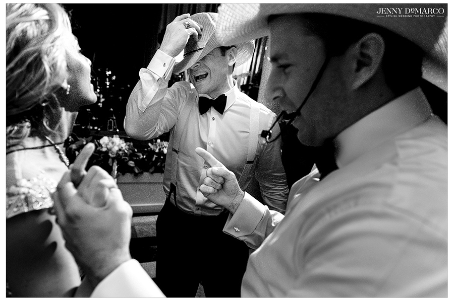Black and white photo of the bride, groom, and wedding guests wearing cowboy hats at the wedding reception.