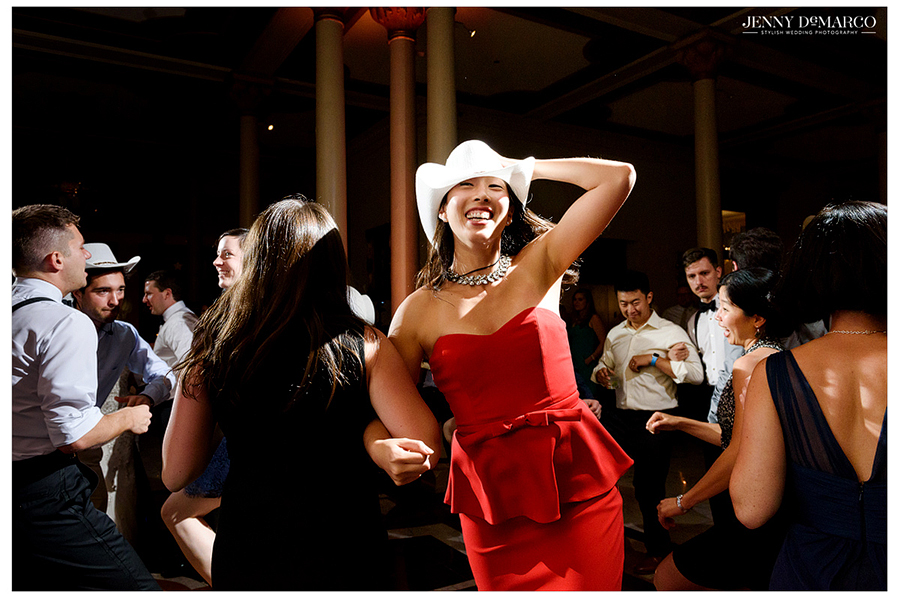 Cowboy hat-wearing wedding guests dance and have fun at the wedding reception