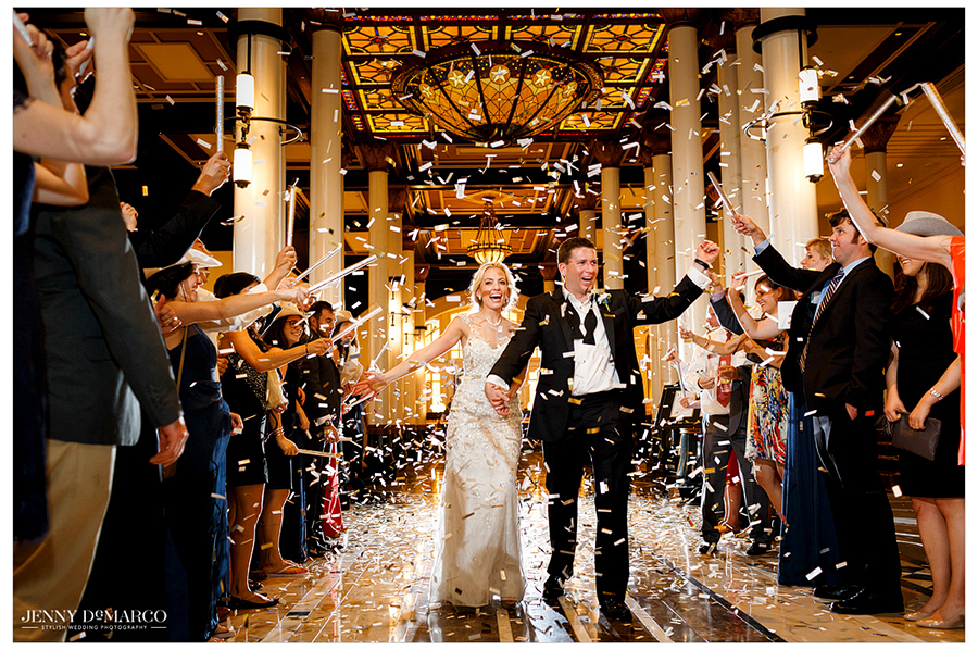 The bride and groom exit the Driskill Hotel amid confetti thrown by their surrounding wedding guests.