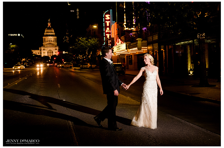 The bride and groom pose together at night on South Congress Avenue with the Texas state capitol building in the background.