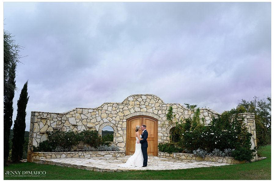 Amy and Dallas embracing in front of the stone altar wall at the Rancho Mirando Luxury Guest Ranch.