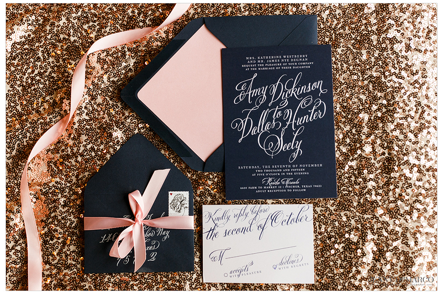 Amy and Dallas's wedding invitations atop a sparkling backdrop.
