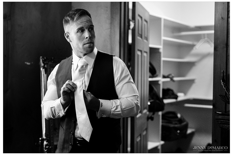 Glamorous shot of the groom fixing his tie as he dresses in his suit.