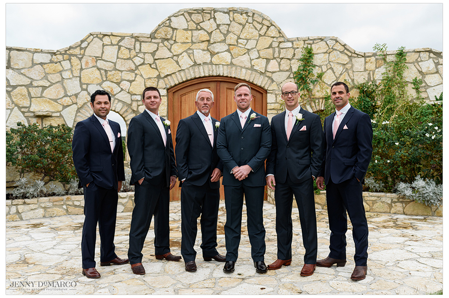 The groomsmen line up for a photo with Dallas in front of the stone altar.