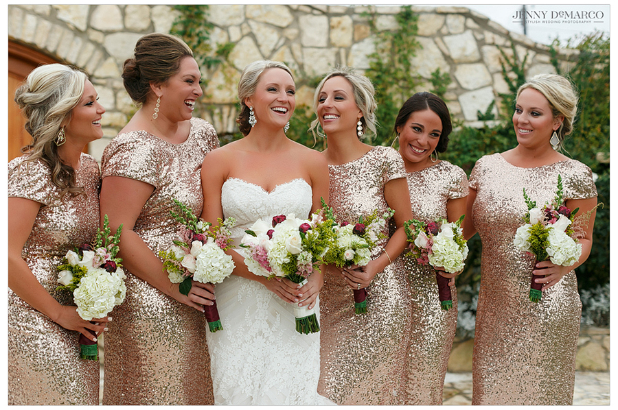 Amy and her bridesmaids share a laugh in their bridal gowns and dresses in front of the stone altar.