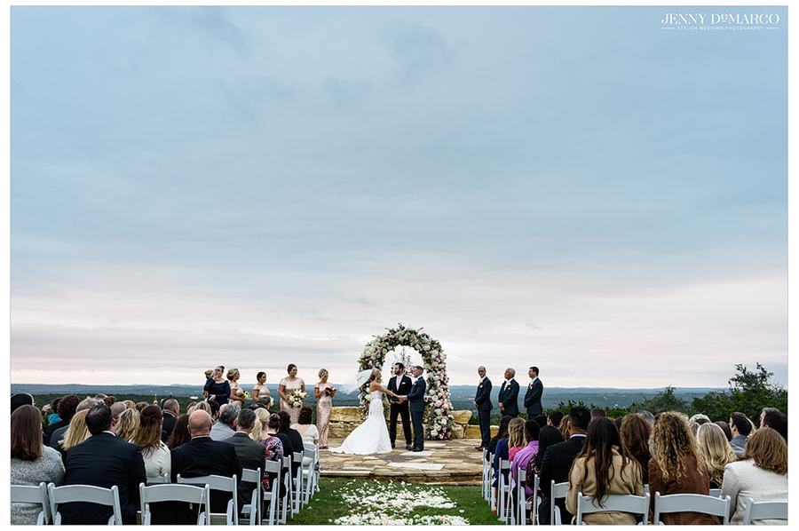 A wide shot of the entire ceremony at the Bella Vista site at sunset shot by Jenny DeMarco, the best Wedding Photographer in Texas.
