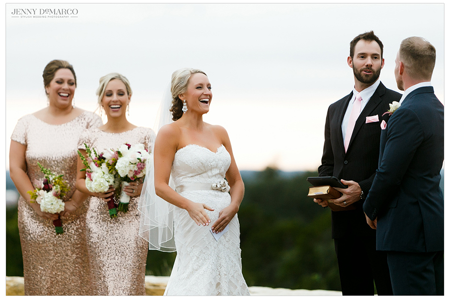 The bride and her bridesmaids laugh as the groom and officiant share a joke.