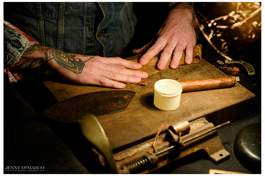 A close-up shot of a craftsman hand-rolling cigars for the guests.