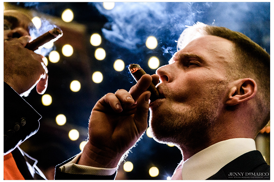 The groom takes a long drag off of his hand-rolled cigar.