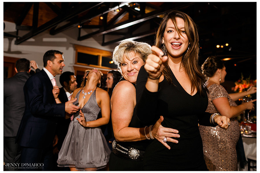 Two female guests laugh and point at the camera while dancing.