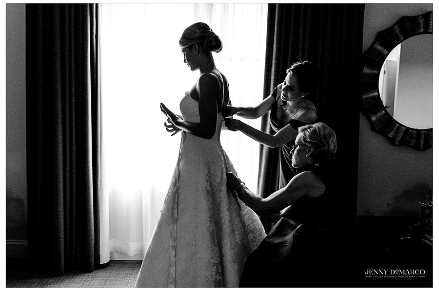 Mother and bridesmaid buttoning the bride's dress in front of the window in black and white.