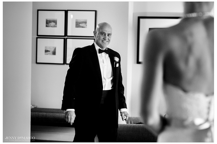 Father of the bride smiles as he sees the bride for the first time in the big reveal in black and white.