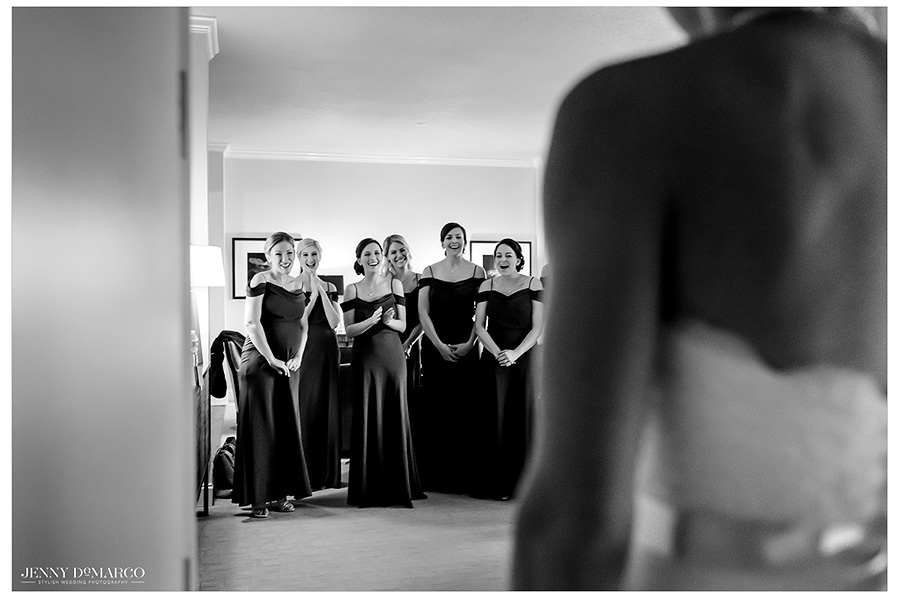 Bridesmaids react as the bride is revealed to them with her complete hair and makeup. The image is in black and white.