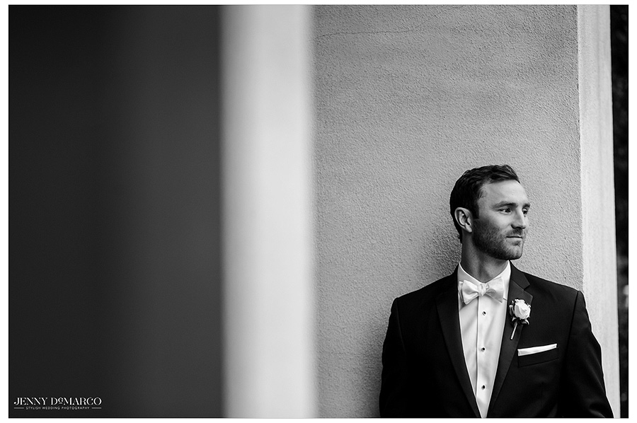 Artistic desaturated image of groom in tux, gazing off into the distance as he waits for his bride.