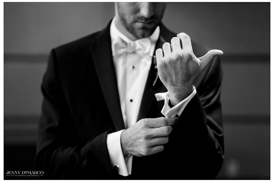 Desaturated image of groom adjusting his cufflinks, a family heirloom. The image does not include the groom's face, but instead draws emotion from the detail of the hands.