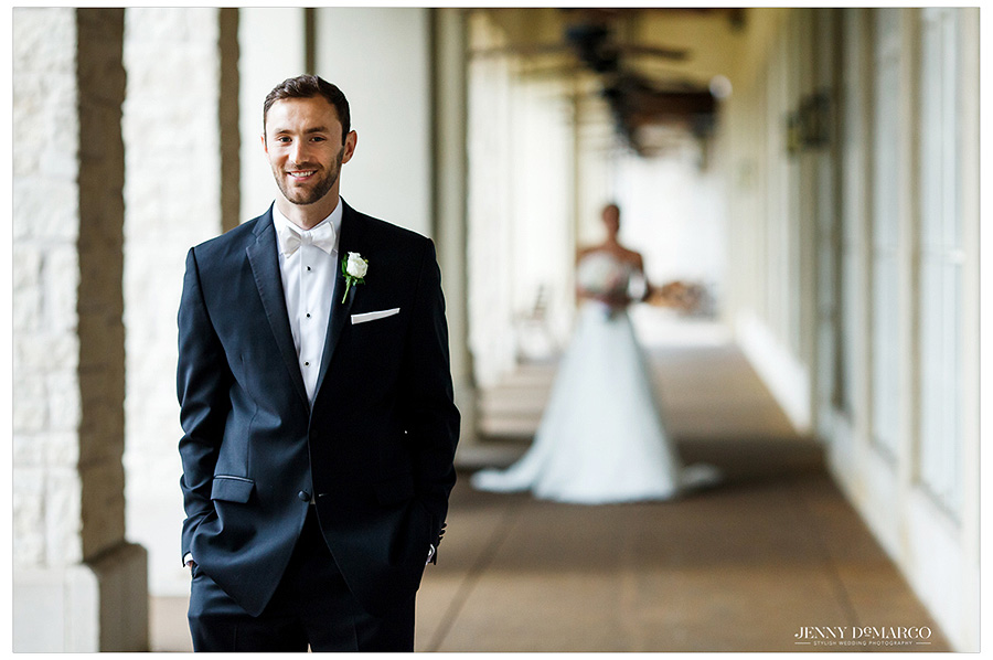 Groom smiles as he waits for his approaching bride to reveal herself to him. The image focuses on the anticipation in the groom's face and the bride is out of focus in the distance.