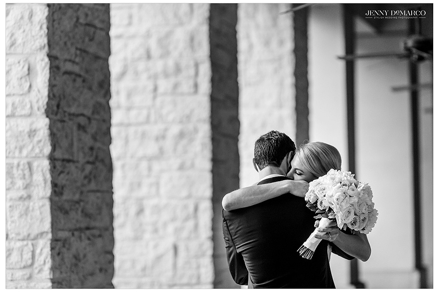 After the first look, Hunter and Kyle lovingly embrace between the columns of the resort. The image is in black and white.