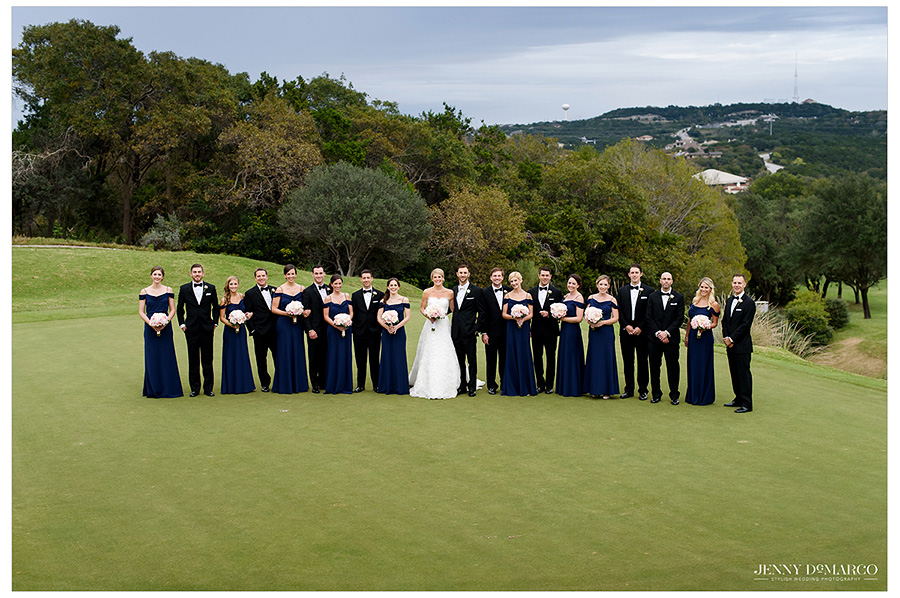 Framed by the lush trees, Hunter and Kyle stand with their complete wedding party on the perfectly manicured golf course.