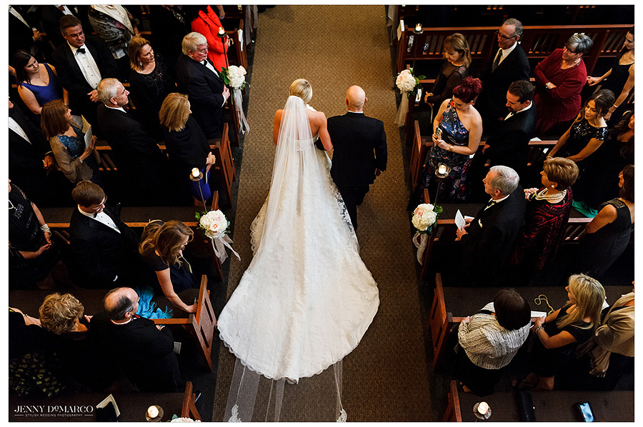 An artistic overhead panorama shows the bride and her father as they walk towards the altar. The focus shifts from the figures in the image to both the bride's veil and the train on the dress.