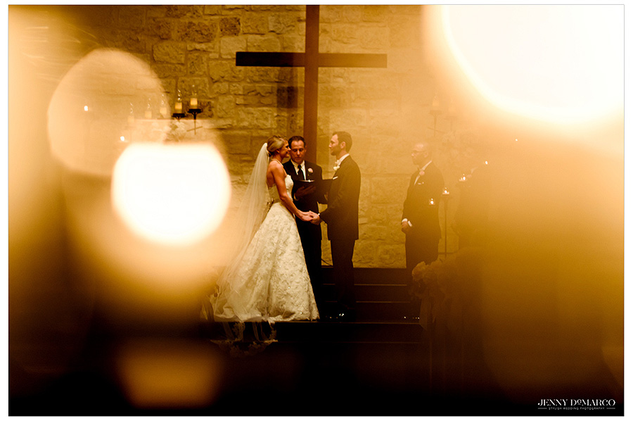 The bride and groom hold hands on the altar. The couple is creatively framed by the glow of the candles.