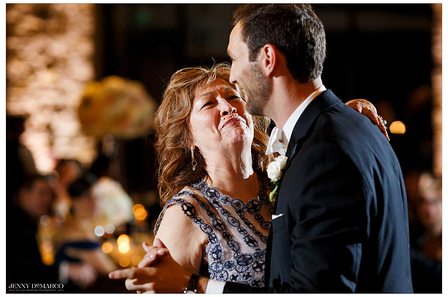 Kyle's mother looks up at her son endearingly as they share a mother and groom dance.