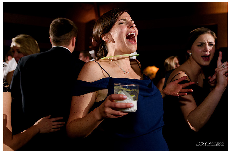 An animated bridesmaid belts out lyrics to a song during the lively reception.