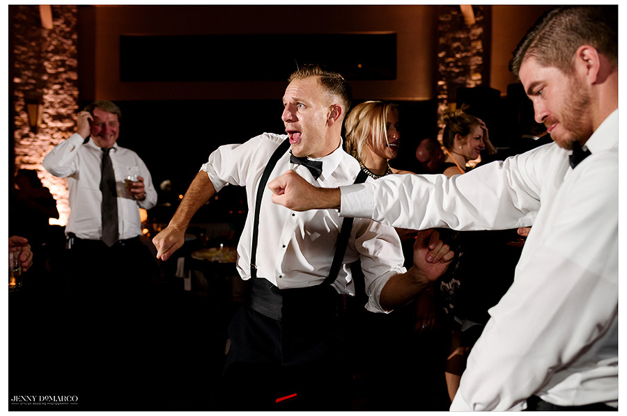 Groomsmen dance together at the party. The energy of the reception is captured in this image.