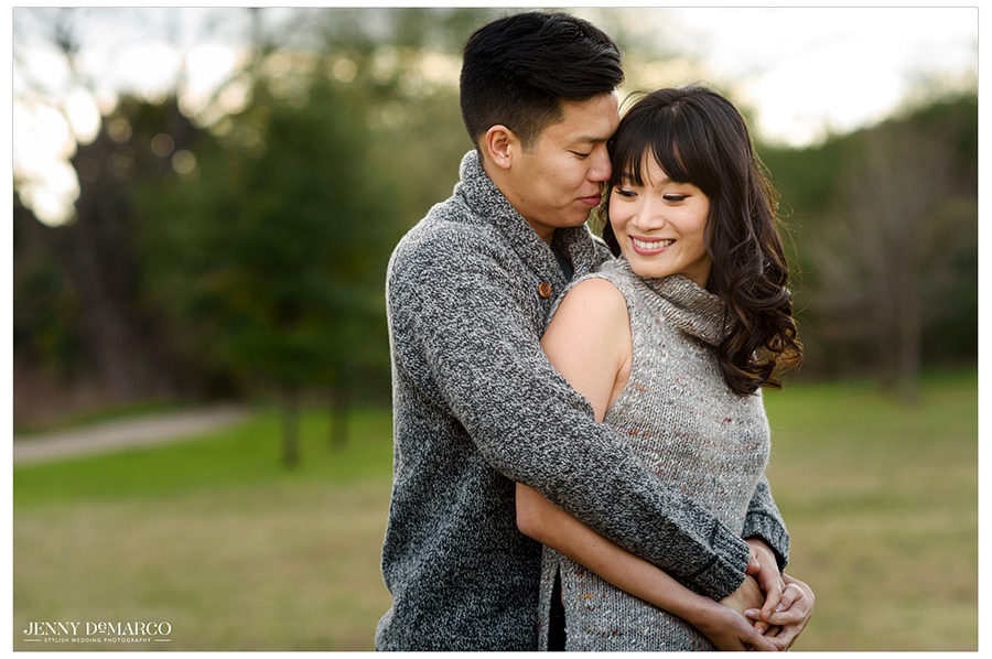 An engaged couple embracing in an austin park
