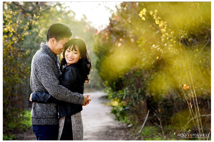 Artfully and colorfully adapted shot by the best wedding photographer in Austin, Jenny DeMarco Photography, of an engaged couple smiling and hugging along a path with fall leaves