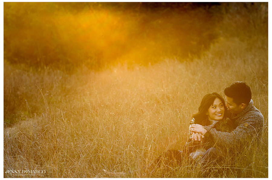 couple lays in the field as the sun sets and smiles at one another