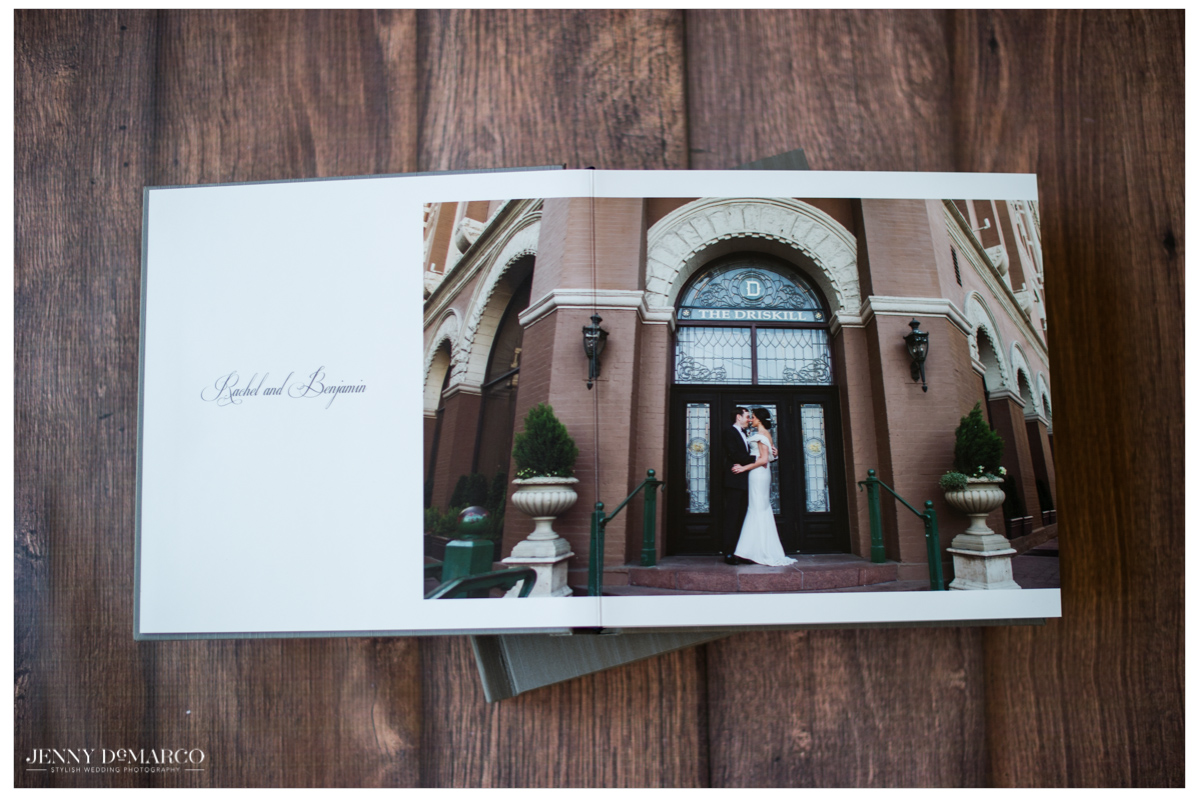 wedding album open to the first introduction page where the bride and groom are kissing outside their wedding venue, the Driskill Hotel in Austin, Texas