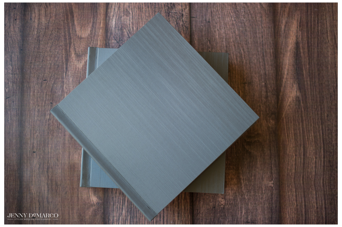 overhead shot of two closed grey silk wedding album covers stacked on top of one another