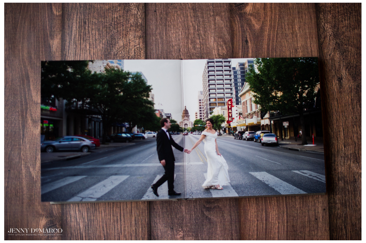 An album open to a full page spread of the bride and groom walking across downtown austin
