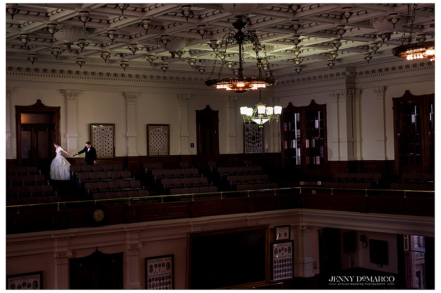 Bride and Groom hold hands before the wedding in the empty Texas State Capitol Senate Chamber.