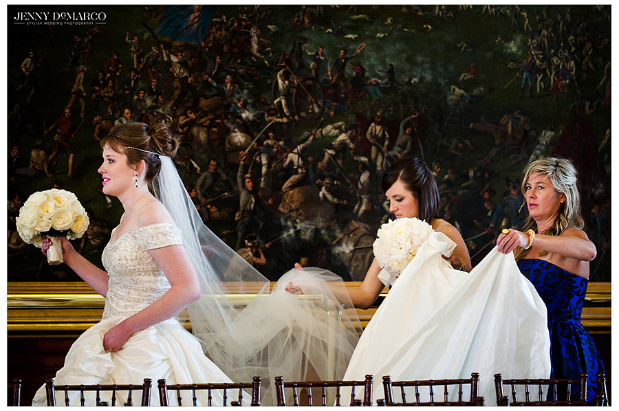 Bride Catherine's two cousins carry her train as she approaches the doors to the Texas State Capitol Senate Chamber.